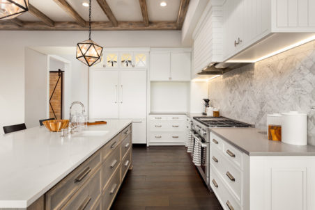 Kitchen with white countertops, white and natural wood cabinets, and exposed beams on the ceiling.