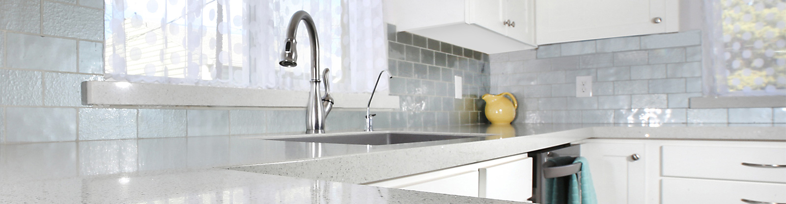 A kitchen with white speckled countertops and a blue brick backsplash. The angle appears as if the camera was set on the countertop.