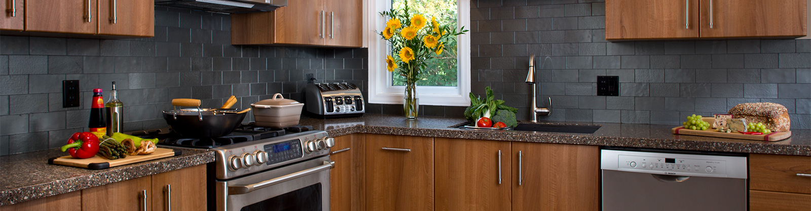A kitchen with wood cabinets, dark gray brick backsplash, a sunflower in a vase and a wok on the stove.