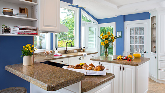 A bright kitchen with brown countertops and blue walls. Sunflowers and muffins are sitting on the counter along with fruit and orange juice.
