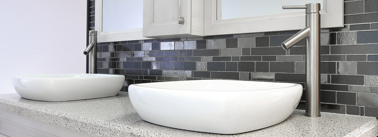 A double bathroom sink with white, raised basins, stainless steel faucets and a gray, brick backsplash.