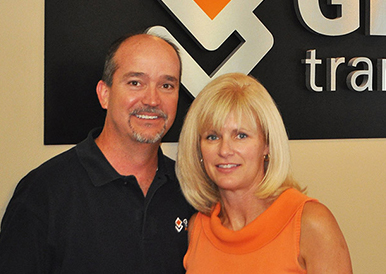 A bald man and blonde woman pose in front of a Granite Transformations sign.