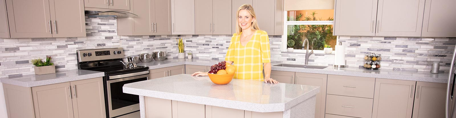 Woman in a yellow shirt standing in a modern kitchen with beige cabinets and white, speckled countertops.