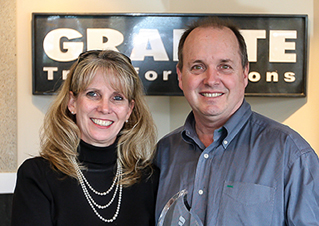 A man and woman standing in front of a Granite Transformations sign.