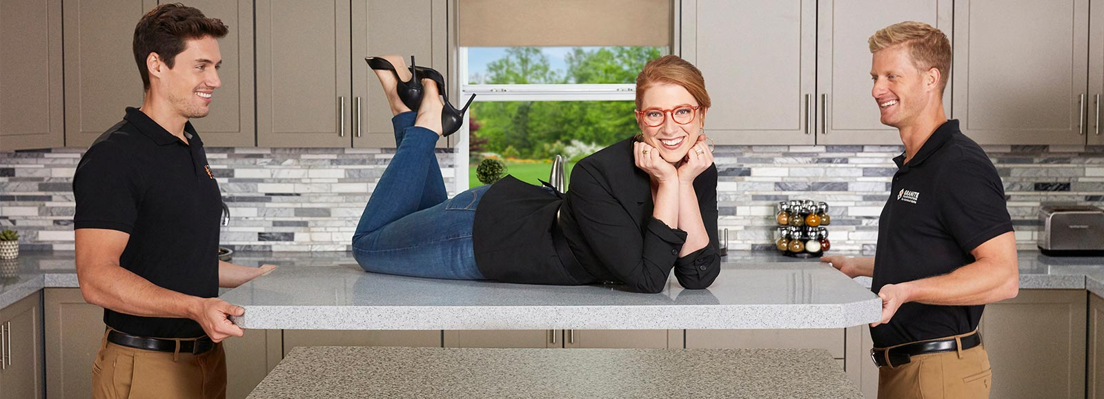 A woman with red hair and red glasses lying on a new countertop being held up by two men on either side of the countertop.