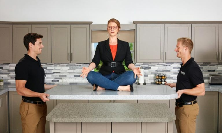 A woman with red hair and red glasses sitting on a new countertop being held up by two men on either side of the countertop.
